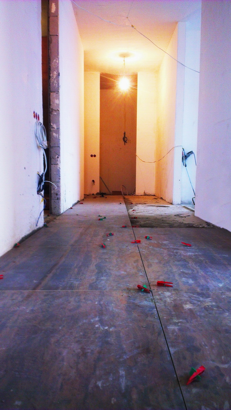 Процесс укладки плитки на коридоре